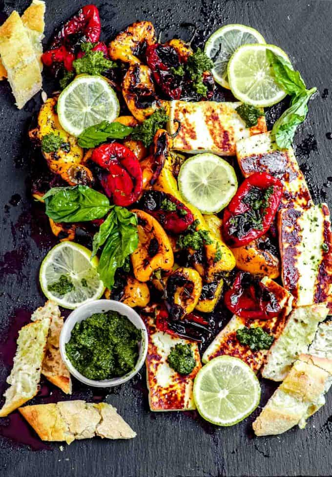 A board of sweet roasted peppers with sliced baguette, pesto and grilled halloumi cheese