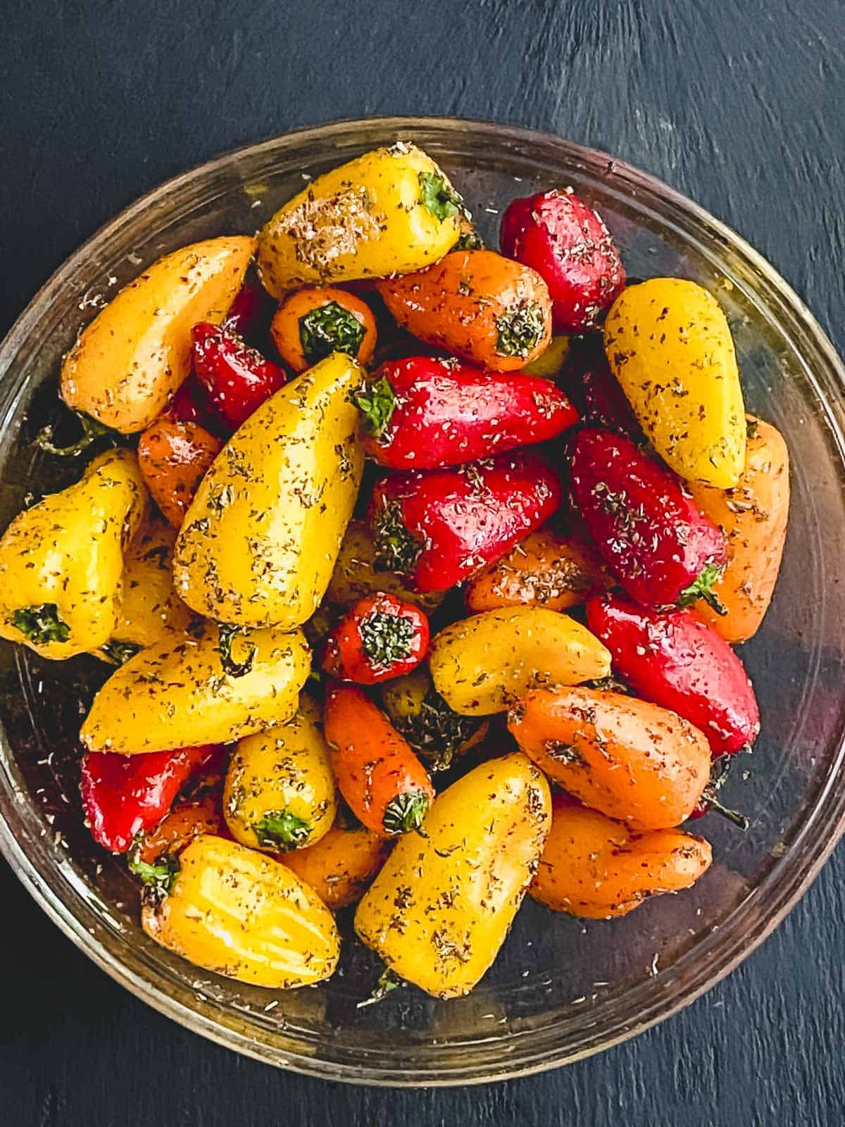 Mini peppers in a bowl with oil and spices