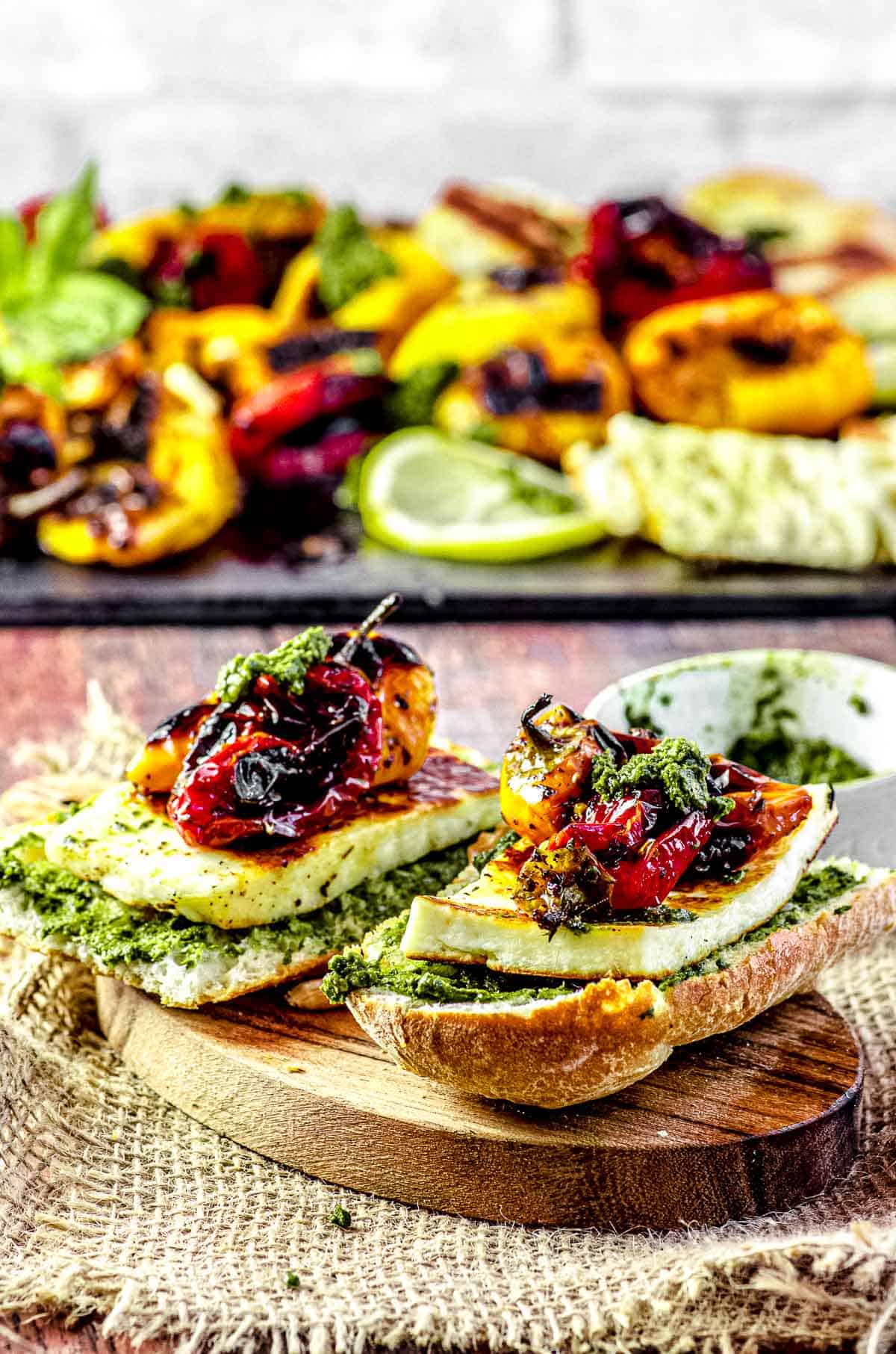 two baguette slices topped with pesto grilled halloumi cheese and roasted mini peppers
