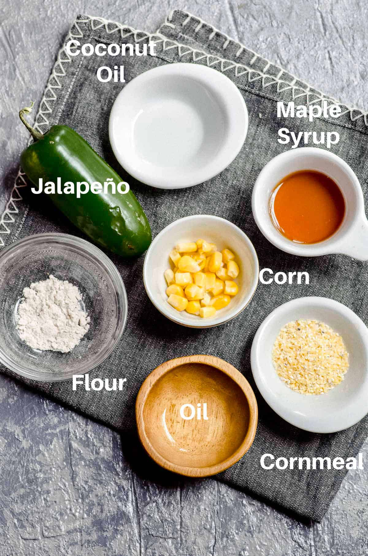 Overhead view of labeled  ingredients for jalapeno vegan cornbread in tiny bowls. Jalapeno, maple syrup, baking powder, corn kernels, corn meal
