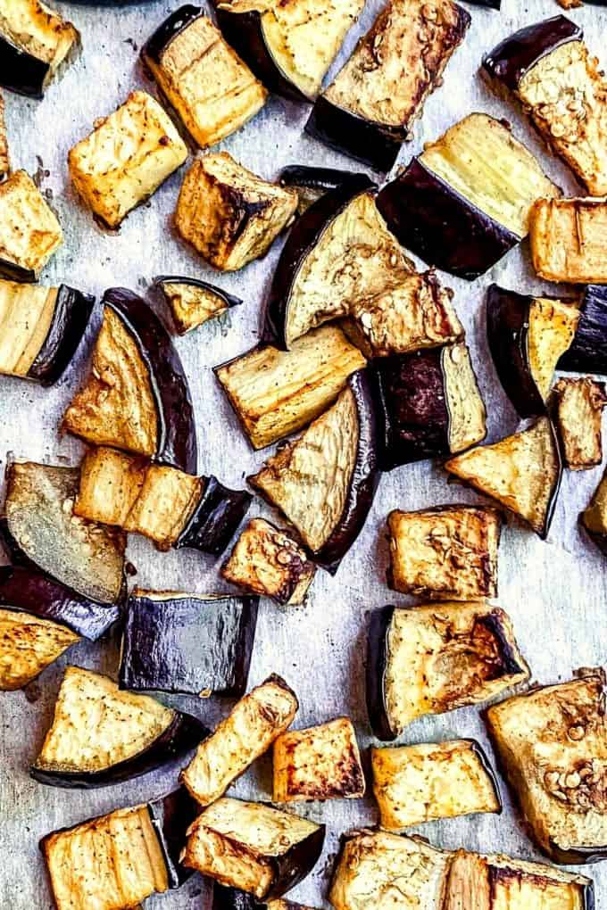 A zoomed up view of cubed roasted eggplant spread onto a parchment lined pan
