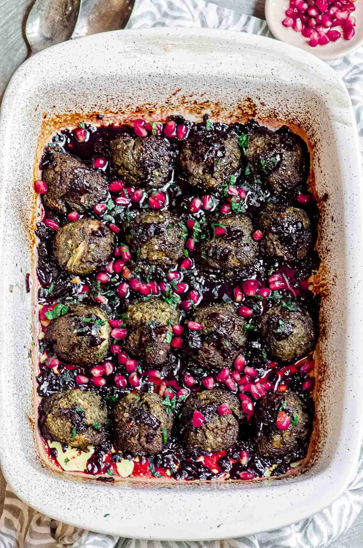 A white baking dish with eggplant meatballs with pomegranate molasses