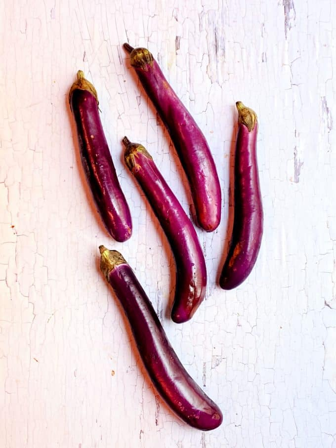 5 Japanese eggplant on a white surface