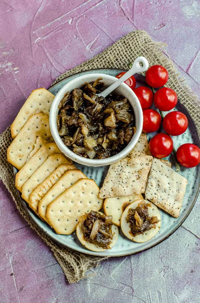 Overhead view of a bowl with apple onion chutney on a plate with some crackers and some cherry tomatoes