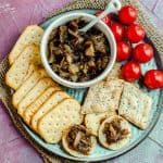 Close up view of a bowl with apple onion chutney on a plate with some crackers and some cherry tomatoes