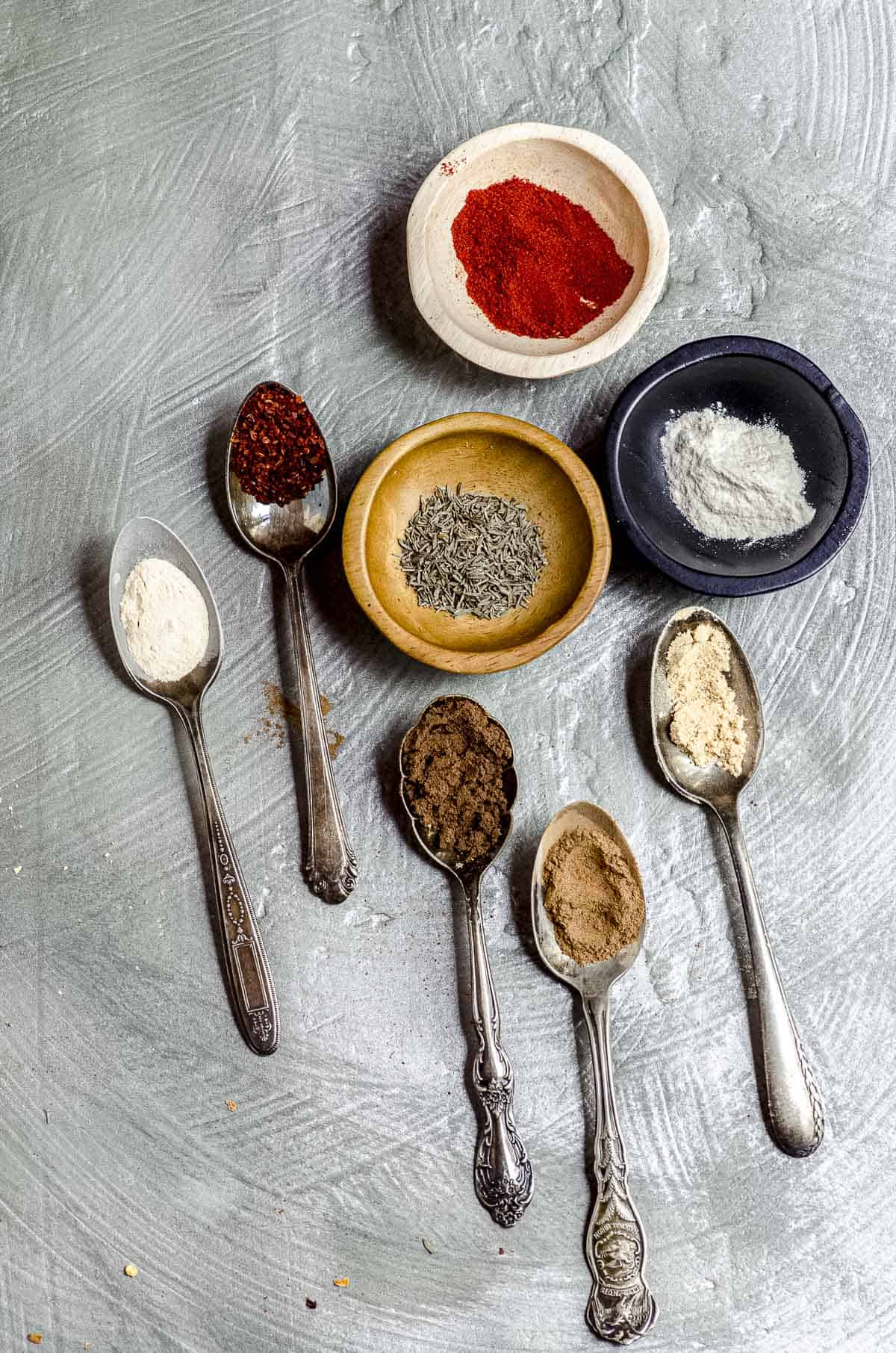 Overhead view of 3 small bowl with spices and some small spoons with spices